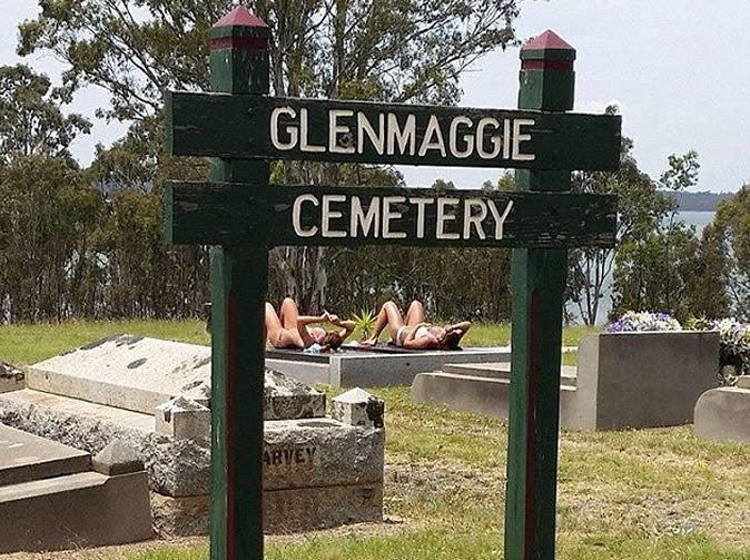 Women in bikinis sunbathe on gravestones
