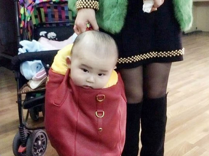 Mum criticised after carrying baby son in designer handbag