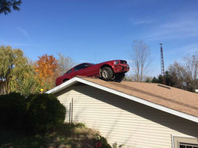 Car lands on house roof after accident