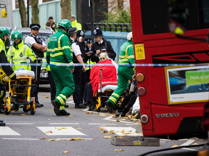 Woman trapped under London bus after it swerved to avoid crash