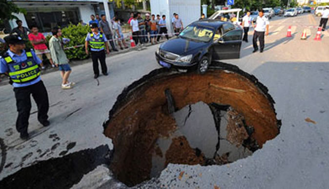 Car almost falls into giant sinkhole