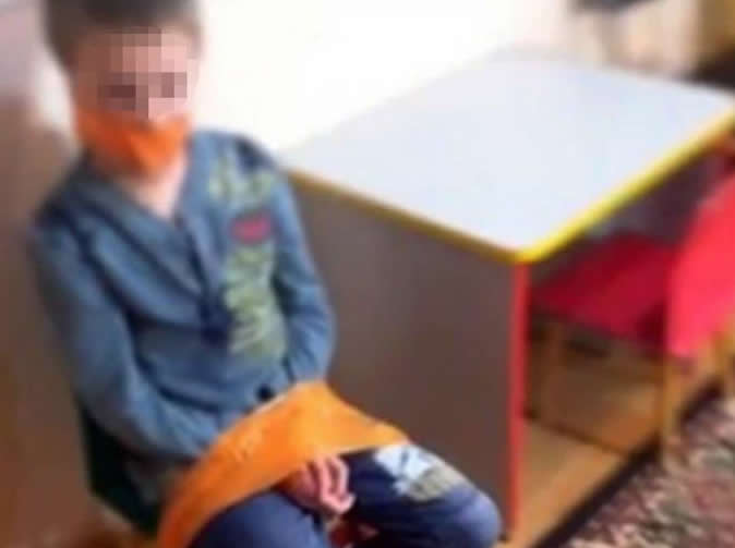 Staff at children's centre tie boy with autism to chair